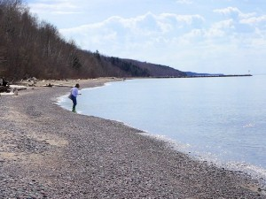 Jo inspecting a find at Black River Harbor's beach to see if it is worthy to keep.